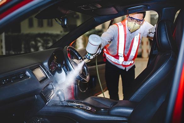 Mann reinigt ein Auto von Innen